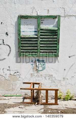 Worn building facade with green shutters and old chair