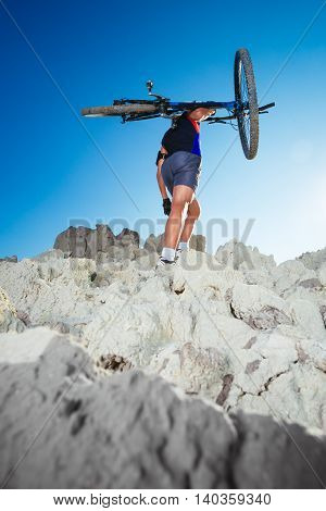 Bicycle rider crossing rocky terrain on the blue sky