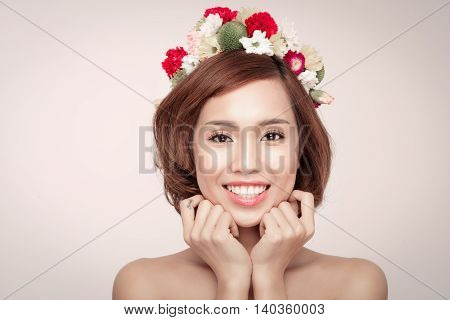 Perfect makeup. Beauty fashion. Spring woman. Beautiful asian woman with flower wreath on her head. Beauty girl with flowers hairstyle.