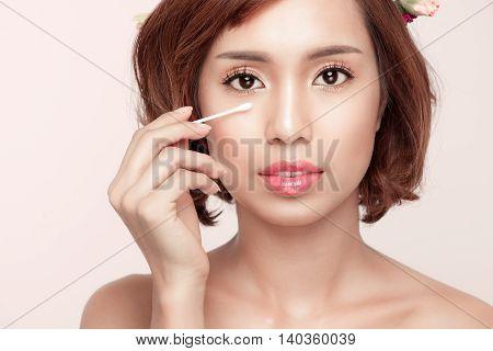 Young beauty removing eyes make-up. Facial closeup of happy smiling beautiful asian woman.