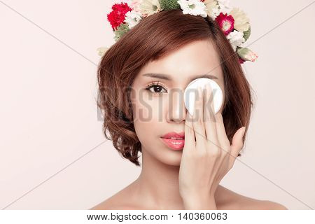 Beauty woman showing cotton swab on face - eye and skin care concept. Facial closeup of happy smiling beautiful