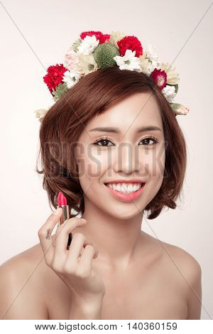 Sensual portrait of a spring woman with flowers on her head holding red lipstick