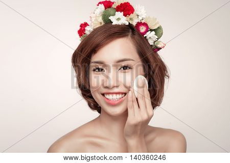 Beauty concept. Beautiful brunette lady removing makeup from her face attractive brunette girl on beige background