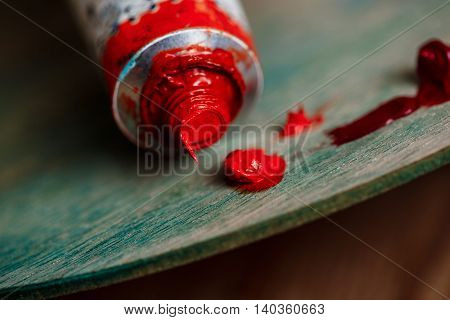 Close up photo of red oil paint on palette over wood background. Copy space.
