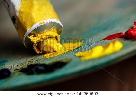 Close up photo of red and yellow oil paints on palette over wood background. Copy space.