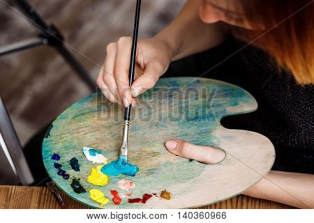 Close up photo of girl mixing oil paints on palette. Copy space.