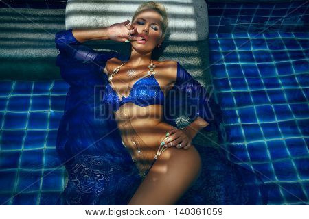 fashion photo of sexy beautiful girl in blue bikini relaxing in pool