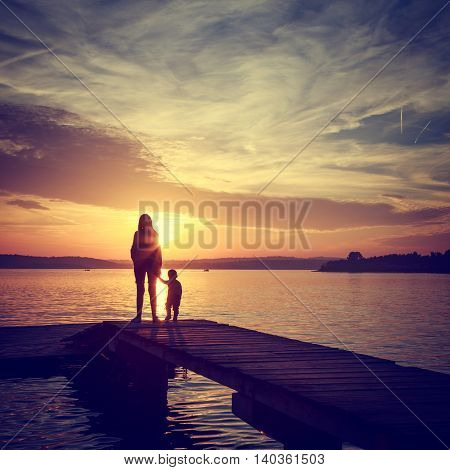 Silhouettes of Young Mother with His Little Baby Standing on the Pier and Watching Sunset by the Sea. Happy Family Lifestyle. Motherhood and Childhood. Mom and Son Concept. Toned Photo. Copy Space.