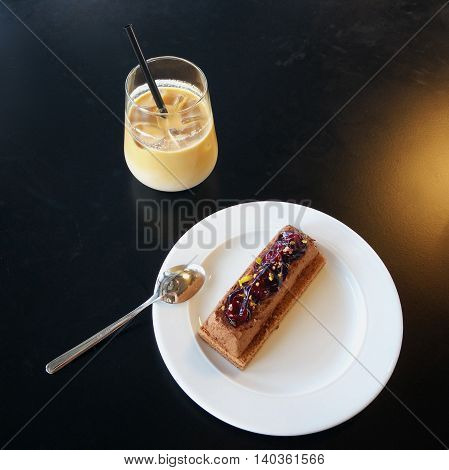 Ice coffee with delicious dessert on white plate put on black background