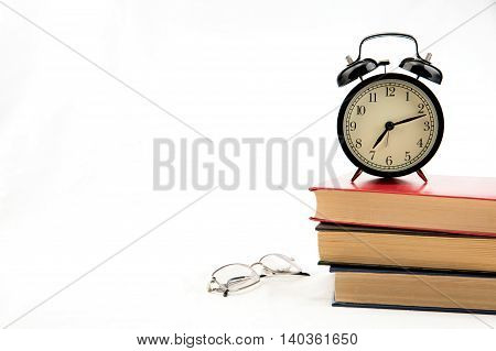 Tree books with alarm clock on white