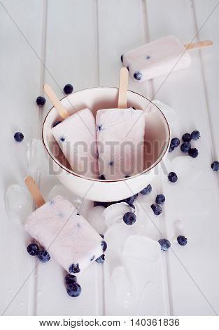 Ice popsicles with yogurt and blueberries in ice lolly mold with wooden sticks