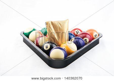 Golden wallet inside colorful billiards's balls on white