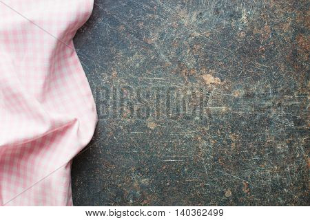 The pink checkered napkin on old kitchen table.