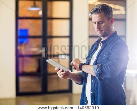 Man checking time while holding digital tablet in creative office