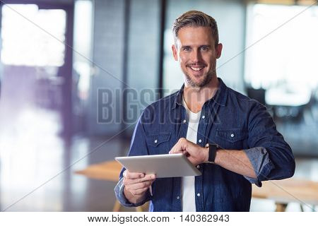 Portrait of smiling man holding digital tablet in creative office