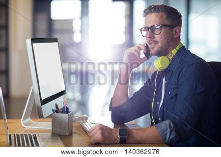 Man talking on phone while sitting by table in office
