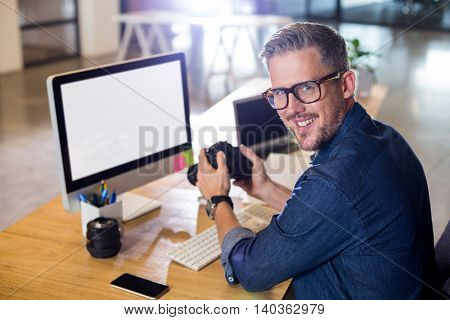 Portrait of smiling man holding camera at table in office
