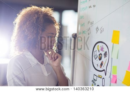 Woman looking at whiteboard in office