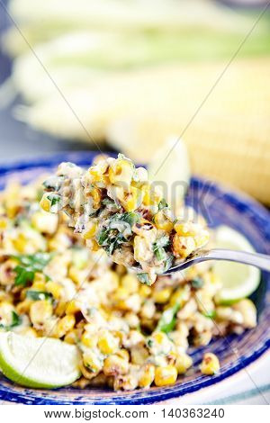 Close up of homemade vegetarian mexican street food corn salad with cilantro, lime, mayonnaise, garlic, chili and cheese on blue plate on stone background. Two corn heads on blured background