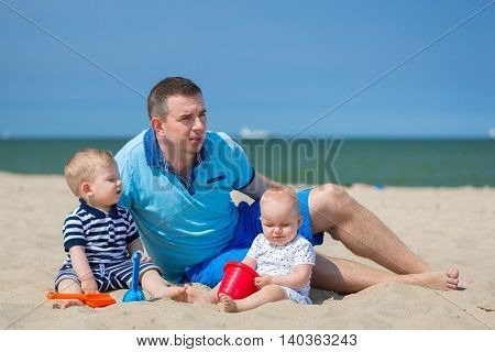 Father with twins playing at the beach of Baltic Sea, Poland