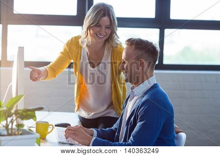 Happy woman discussing with man in creative office