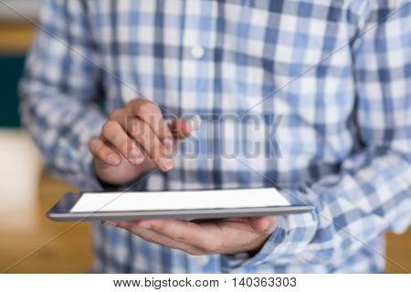 Mid section of man using digital tablet at cafe
