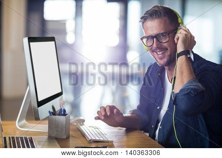 Portrait of smiling man with headphones sitting by table in office