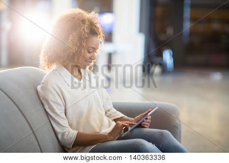 Woman using digital tablet while sitting on sofa in office