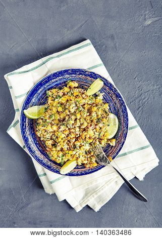 Top view vegetarian mexican street food corn salad with cilantro, lime, mayonnaise, garlic, chili and cheese on blue vintage plate on stone background. Sweet, sour and hot tastes from mexican cuisine