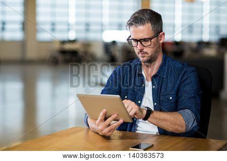 Focused man using digital tablet in creative office