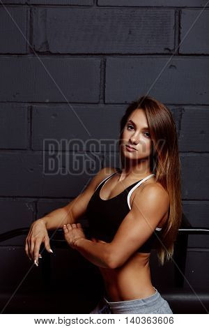 Attractive young woman in sportswear posing on black background. Healthy female model with muscular body in studio.