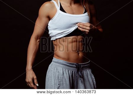 Muscular body of a young woman, abs close up. Woman's abs
