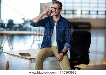 Man talking on phone while sitting on table in office