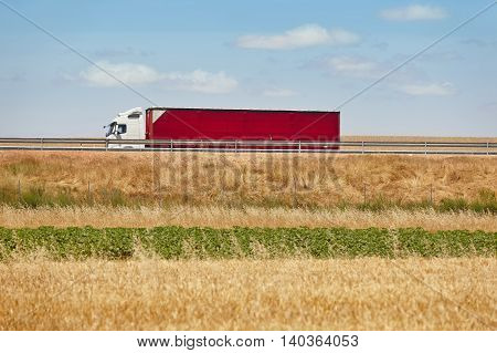 Red heavy truck on the road. Delivery cargo logistic. Spain. Horizontal