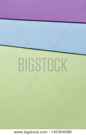 Colored cardboards background in green blue purple tone. Copy space. Vertical