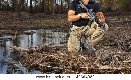 Man with an AR-15 and handgun kneeling next to some water
