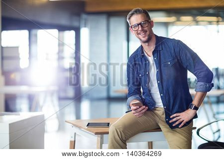 Portrait of man using mobile phone while sitting on table in office
