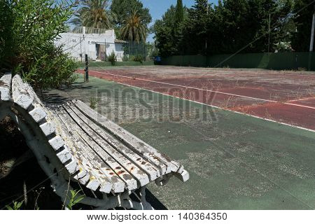 Abandoned or deserted tennis court with bench