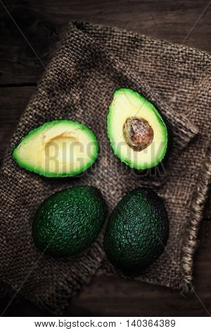 Halved and whole avocado on a dark wood background. Rustic country style