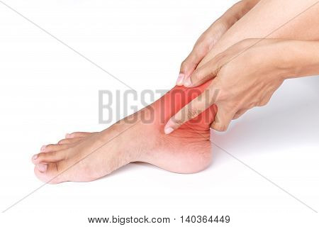Ankle sprain.Female holding hand to spot of Ankle pain on white background.