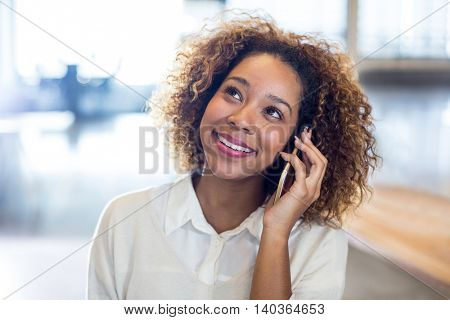 Smiling woman with curly hair talking on phone in office