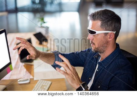 Man wearing virtual reality glass by table in office