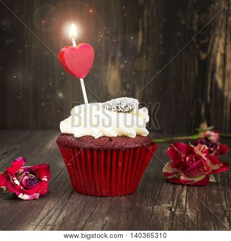 Delicious red velvet cupcake with burning candle. Anniversary, valentines day greeting card. Toned image. Selective focus