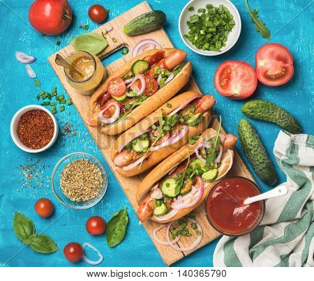 Homemade hot-dogs on wooden serving board with fresh vegetables, spices, ketchup and mustard over blue painted background, top view