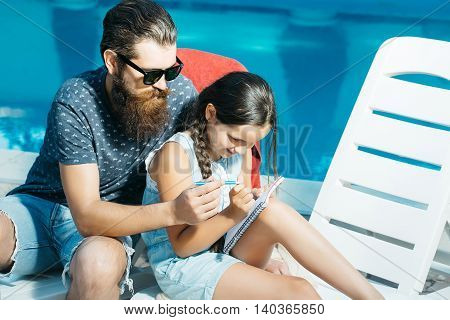 young handsome bearded man with long beard in sun glasses on face on beach chair and small happy girl with pen and notebook at swimming pool with blue water sunny summer vacation