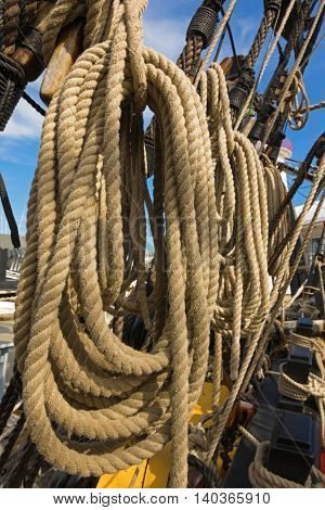 Closeup of rolled thick ropes on the old ship near wooden cleats