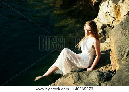 young pretty woman in white wet dress in water near stone sunny day outdoor on natural background
