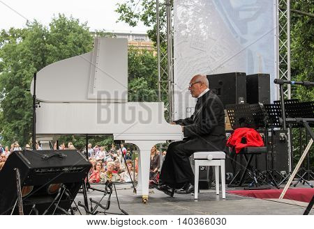 St. Petersburg, Russia - 23 July, Maestro behind a white grand piano, 23 July, 2016. Speech by David Goloschekin with his jazz group on the Arts Square in St. Petersburg.