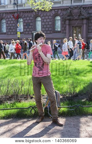 St. Petersburg, Russia - 9 May, A street musician playing the flute, 9 May, 2016. Vacationers people on the lawns and gardens in the city.