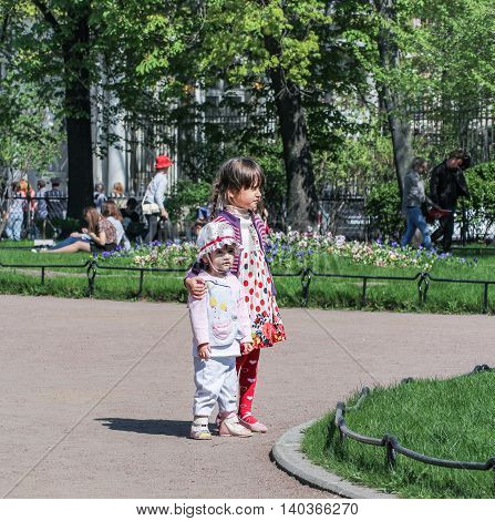 St. Petersburg, Russia - 9 May, Children in flower beds in the garden, 9 May, 2016. Vacationers people on the lawns and gardens in the city.